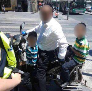אב מרכיב את שני ילדיו על אופניים חשמליים (צילום: דוברות המשטרה)