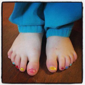 כפות רגליים של ילד/ה עם לק על הציפורניים בצבעי דגל הגאווה (צילום: טל כפיר שור)