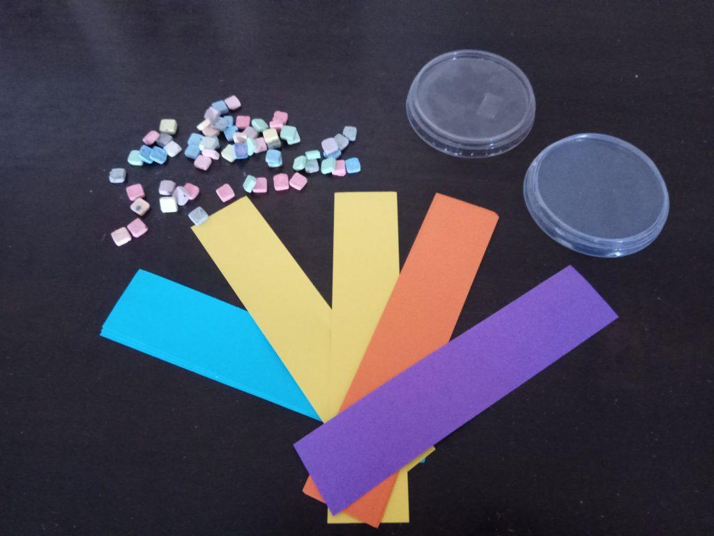 חומרי יצירה זמינים - מכסים של גבינה, אבני פסיפס, ושאריות דפים (צילום: מיכל פישמן-רואה)