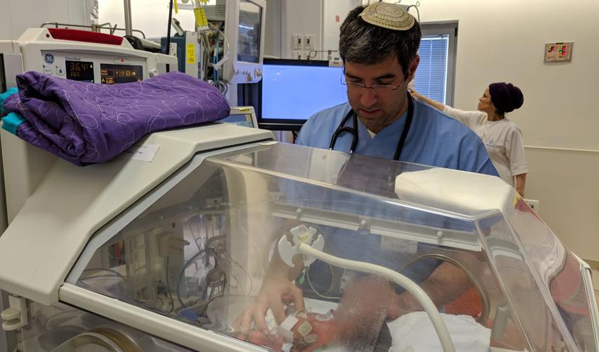 """ד""""ר יאיר קסירר והתינוק (צילום: שערי צדק)"""