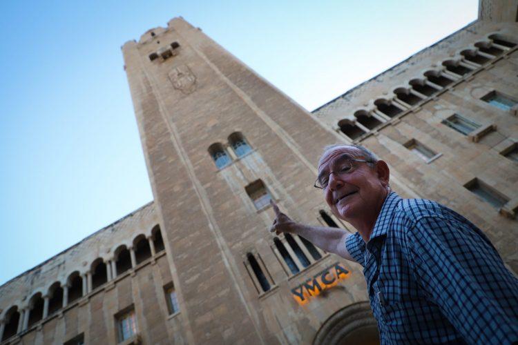 """נגן הפעמונייה גבי שפלר מצביע לכיוון חדר הפעמונים במגדל ימק""""א (צילום: באדיבות מנהל התרבות של ימק""""א)"""