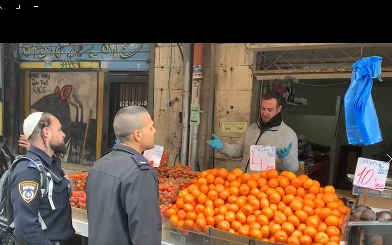 שוטרים מבקשים מבעל דוכן בשוק לסגור (צילום: רון ירקוני יחסי ציבור)