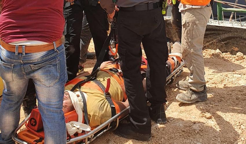 חילוץ הפועל מתוך הבור באתר הבנייה במרכז העיר (צילום: כבאות והצלה ירושלים)