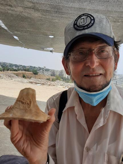 """ד""""ר אדם אקרמן אוחז באחת מטביעות החותם שהתגלו (צילום: עצמי)"""