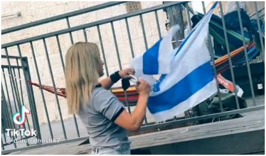 תיעוד של צעירה משחיתה את דגל ישראל (צילום: מתוך טיקטוק; רץ ברשת מפורסם לפי סעיף 27 א לחוק זכויות היוצרים להוספת קרדיט נא לפנות למערכת)