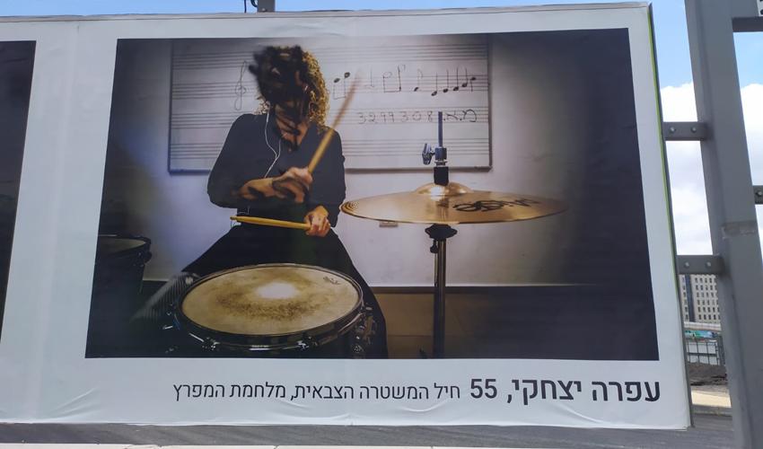 פניה של המוזיקאית עפרה יצחקי מושחרות בשלט חוצות בכניסה לעיר (צילום: שלומי הלר)