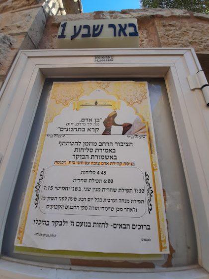 """לוח הודעות לזמני התפילה בבית כנסת עדס (צילום"""" ד""""ר אדם אקרמן)"""